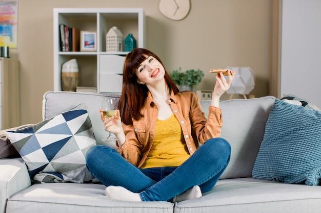 Heureuse jeune fille souriante en jeans et chemise jaune, tenant un verre de vin et un morceau de pizza, assis sur un canapé gris avec des oreillers à la maison