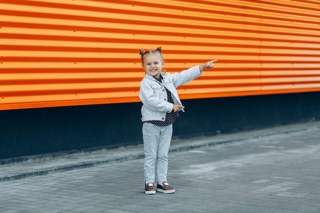 Heureuse jeune fille souriante en jeans pointant avec ses doigts