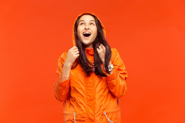 L'heureuse jeune fille souriante posant au studio en veste orange automne isolé sur mur orange