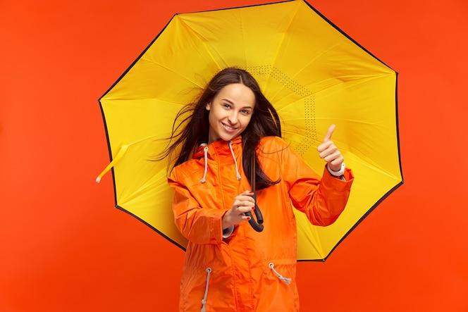L'heureuse jeune fille souriante posant au studio en veste orange automne isolé sur rouge. émotions positives humaines. concept du temps froid. concepts de mode féminine