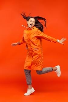 L'heureuse jeune fille souriante posant au studio en veste orange automne isolé sur rouge.