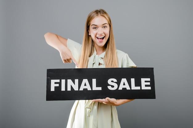 Heureuse jeune fille souriante avec signe de vente finale isolé