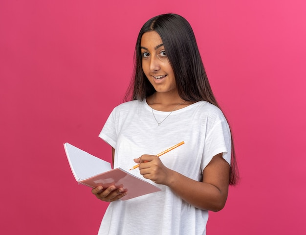 Heureuse jeune fille en t-shirt blanc tenant un cahier et un crayon regardant la caméra avec le sourire sur le visage