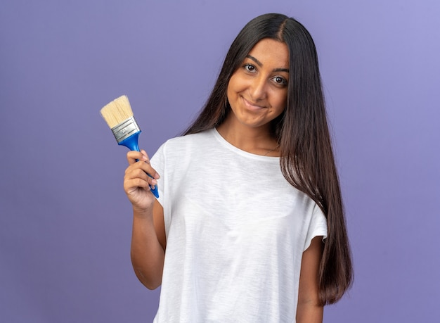 Heureuse jeune fille en t-shirt blanc tenant un pinceau regardant la caméra avec le sourire sur le visage debout sur fond bleu