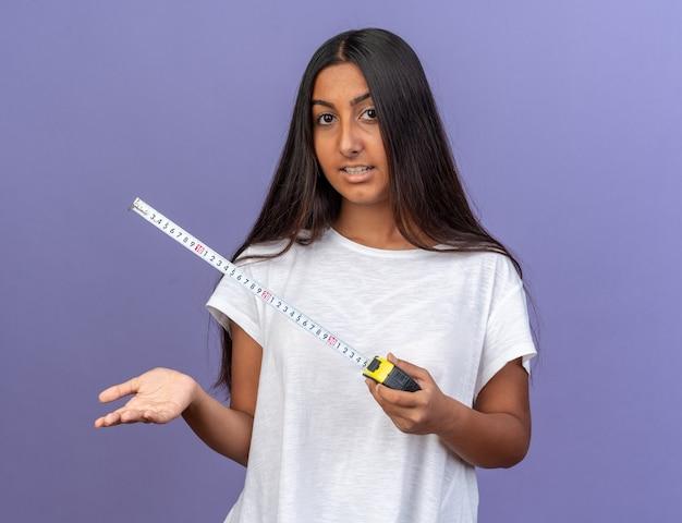 Heureuse jeune fille en t-shirt blanc tenant un ruban à mesurer regardant la caméra avec un sourire sur le visage debout sur fond bleu