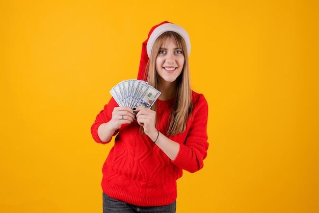 Heureuse jeune fille tenant des billets de cent dollars portant un bonnet de noel