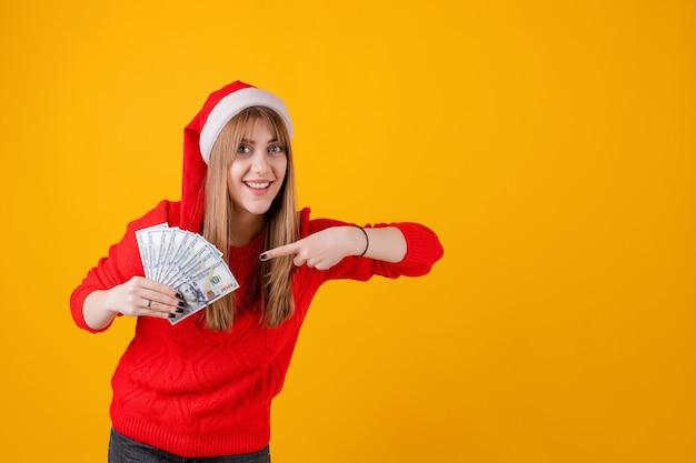 Heureuse jeune fille tenant des billets d'un dollar dans la main, pointant le doigt sur eux portant bonnet