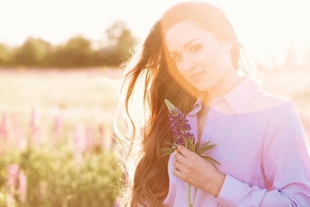 Heureuse jeune fille tenant une fleur de lupin dans les mains.