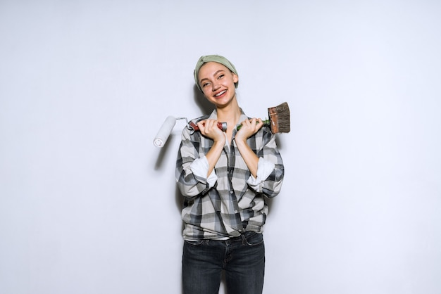 Heureuse jeune fille tenant un rouleau et un pinceau pour peindre les murs de son nouvel appartement