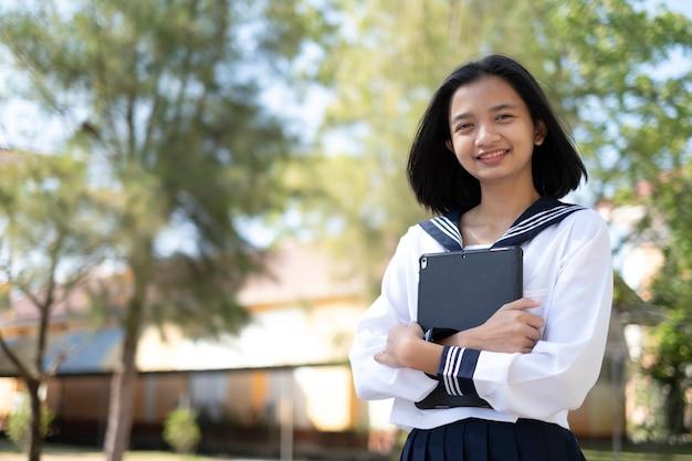 Heureuse jeune fille tenir un ordinateur portable à l'école