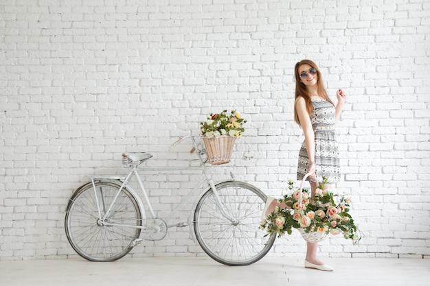 Heureuse jeune fille avec vélo vintage et fleurs