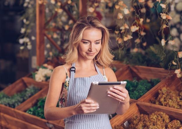 Heureuse jeune fleuriste blonde regardant tablette numérique