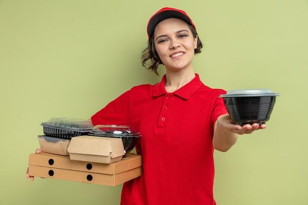 Heureuse jeune jolie livreuse tenant un contenant de nourriture et un emballage sur des boîtes à pizza