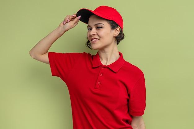 Heureuse jeune jolie livreuse tenant sa casquette et
