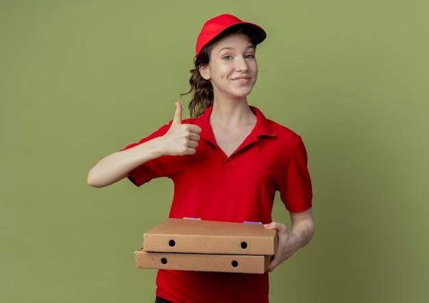 Heureuse jeune jolie livreuse en uniforme rouge et casquette tenant des colis de pizza et montrant le pouce vers le haut