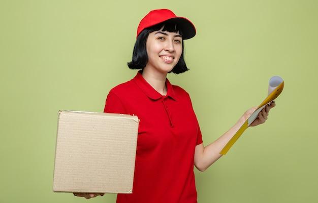 Heureuse jeune livreuse caucasienne tenant une boîte en carton et un presse-papiers