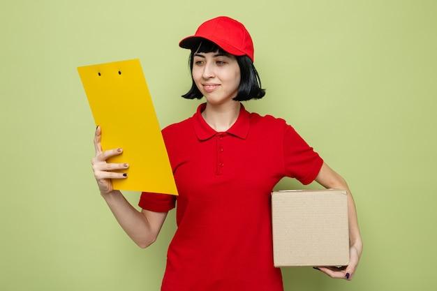Heureuse jeune livreuse caucasienne tenant une boîte en carton et regardant le presse-papiers