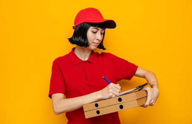 Heureuse jeune livreuse caucasienne tenant des boîtes à pizza et écrivant sur le presse-papiers