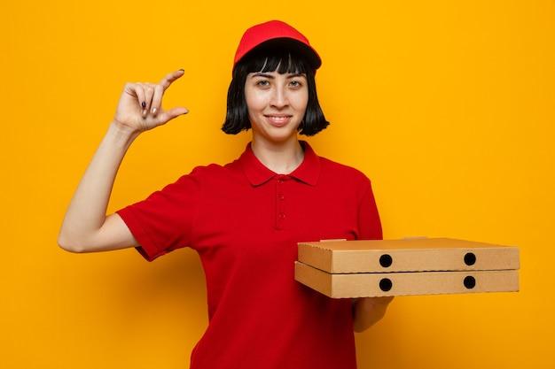 Heureuse jeune livreuse caucasienne tenant des boîtes à pizza et faisant semblant de garder quelque chose