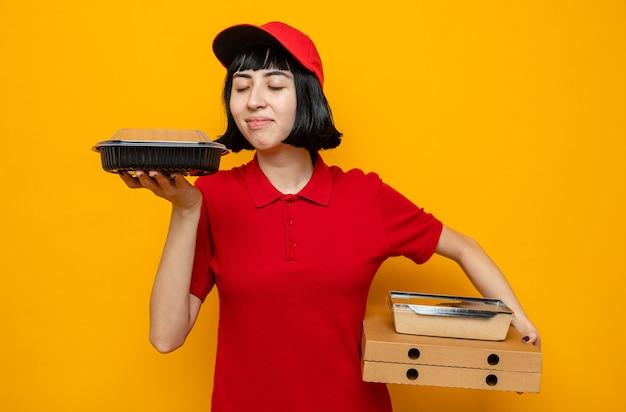 Heureuse jeune livreuse caucasienne tenant un récipient de nourriture et un emballage sur des boîtes à pizza