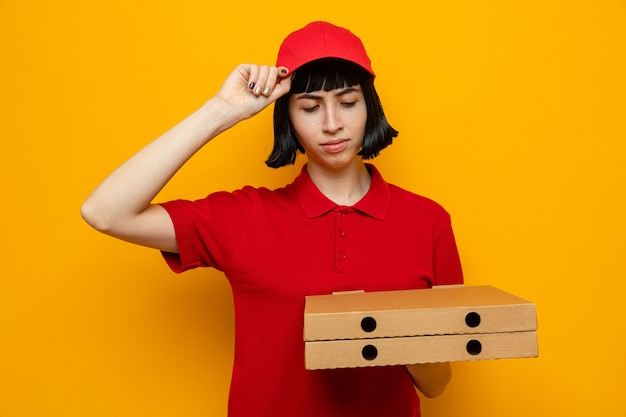 Heureuse jeune livreuse caucasienne tenant et regardant des boîtes à pizza