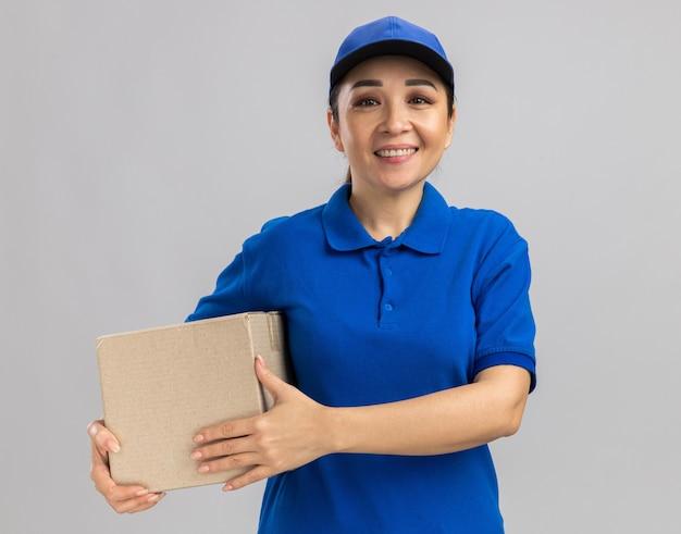 Heureuse jeune livreuse en uniforme bleu et casquette tenant une boîte en carton avec un sourire sur le visage debout sur un mur blanc