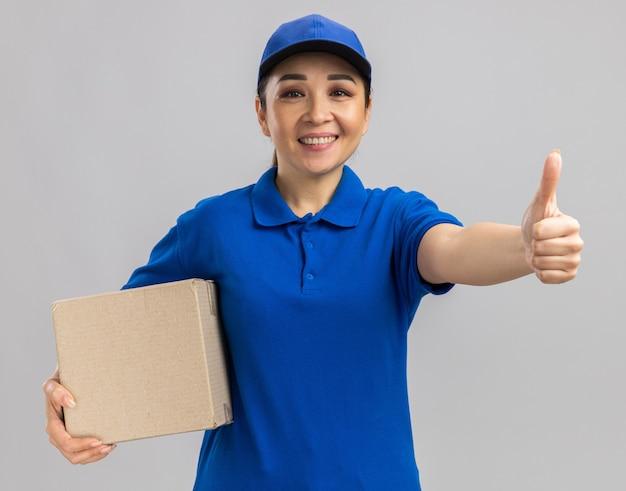 Heureuse jeune livreuse en uniforme bleu et casquette tenant une boîte en carton avec un sourire sur le visage montrant les pouces vers le haut
