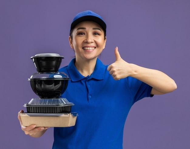 Heureuse jeune livreuse en uniforme bleu et casquette tenant une pile de colis alimentaires souriant joyeusement montrant les pouces vers le haut debout sur le mur violet