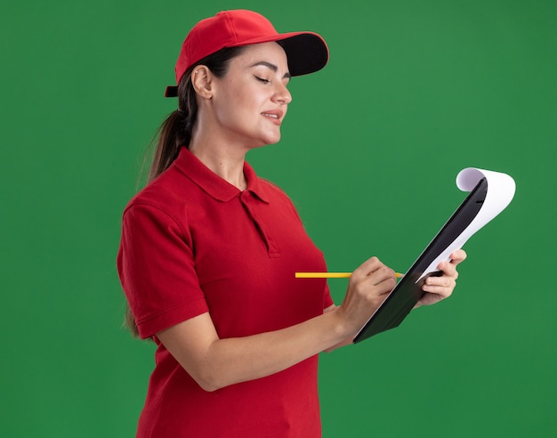 Heureuse jeune livreuse en uniforme et casquette