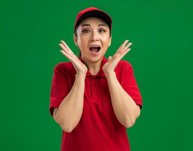 Heureuse jeune livreuse en uniforme rouge et casquette étonnée et surprise debout sur un mur vert