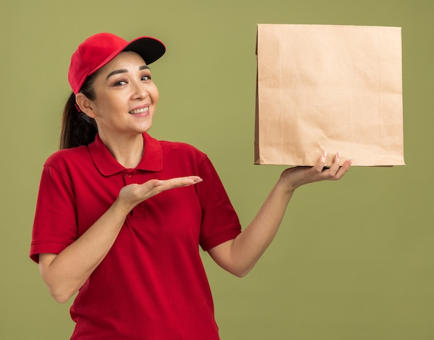 Heureuse jeune livreuse en uniforme rouge et casquette tenant un paquet de papier avec un sourire sur le visage présentant le bras de la main debout sur un mur vert