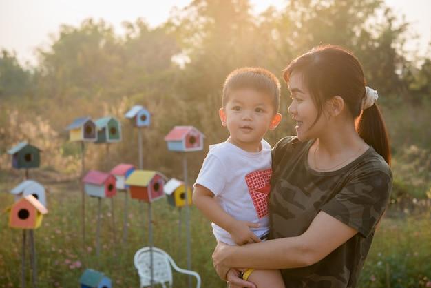 Heureuse jeune maman joue et s'amuse avec son petit bébé dans le parc par une journée d'été ensoleillée