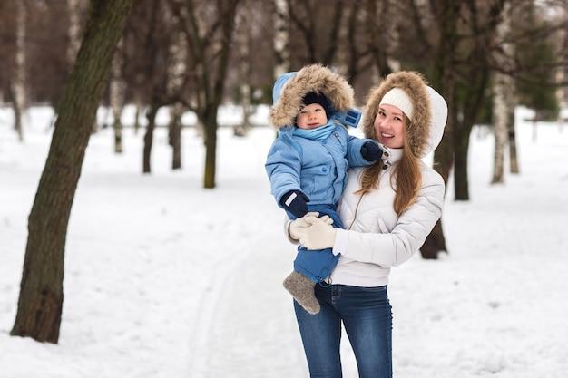 Heureuse jeune maman marchant avec son bébé dans le parc en hiver