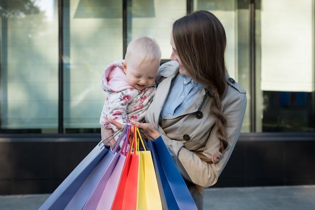 Heureuse jeune maman avec petite fille sur les bras et sacs à provisions à la main. jour de shopping. centre commercial