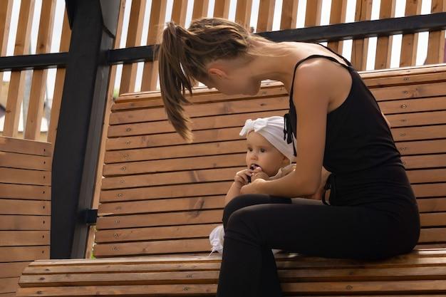Heureuse jeune maman avec sa petite fille jouant sur un banc de parc