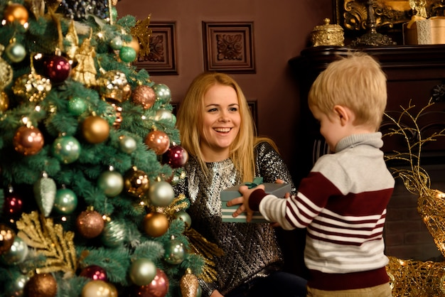 Heureuse jeune maman et son fils à la maison avec un arbre de noël