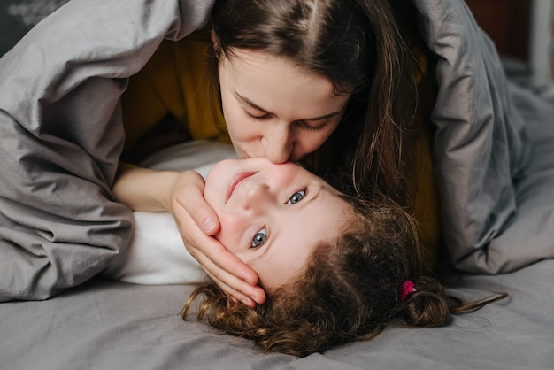 Heureuse jeune mère aimante embrassant la mignonne petite fille allongée sur le lit, savourez le temps ensemble à la maison, exprimant l'amour, souriant maman et enfant fille s'amusant à jouer, concept de relations chaleureuses