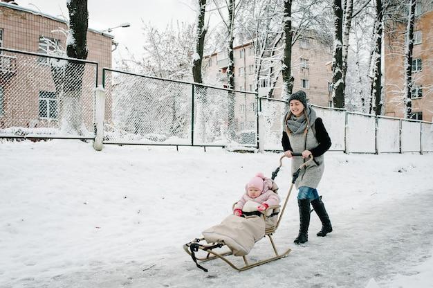 Heureuse jeune mère courir avec bébé et un traîneau pour enfants à l'extérieur sur le fond de l'hiver.
