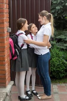 Heureuse jeune mère embrassant ses filles avant d'aller à l'école