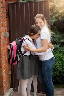 Heureuse jeune mère embrassant ses filles avant de partir pour l'école