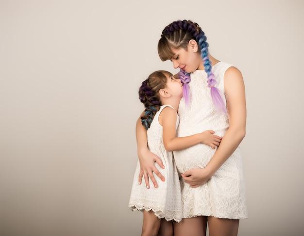 Heureuse jeune mère enceinte tient et embrasse sa petite fille dans les mêmes tenues et coiffures