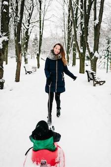 Heureuse jeune mère et enfants garçon, fils sur des traîneaux à pied et jouer dans le parc d'hiver.
