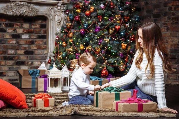 Heureuse jeune mère et fille avec des cadeaux de noël