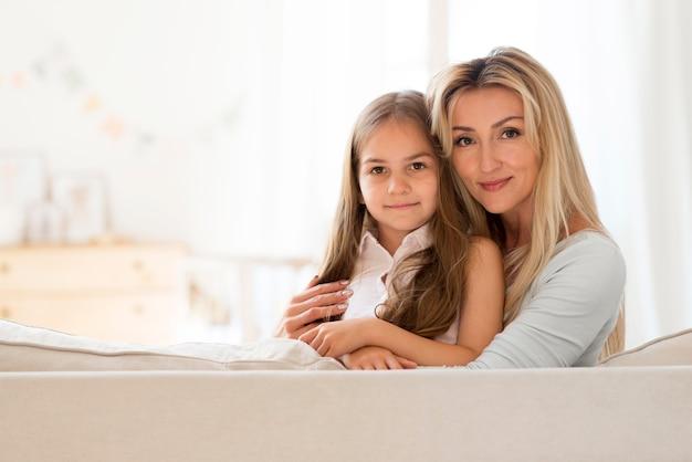 Heureuse jeune mère et fille posant ensemble