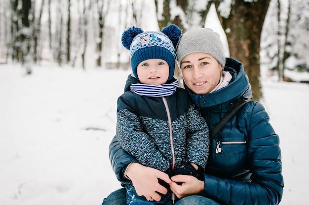 Heureuse jeune mère avec fils à pied dans le parc d'hiver.