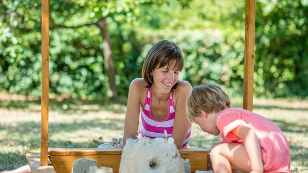 Heureuse jeune mère jouant avec son enfant dans le jardin
