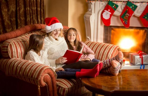 Heureuse jeune mère lisant un livre à deux filles à la cheminée