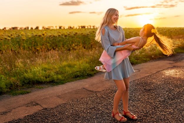 Heureuse jeune mère mince tourne avec sa petite fille joyeuse