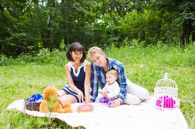 Heureuse jeune mère et père avec leur petite fille se détendre sur une couverture dans un parc célébrant avec un gâteau d'anniversaire.