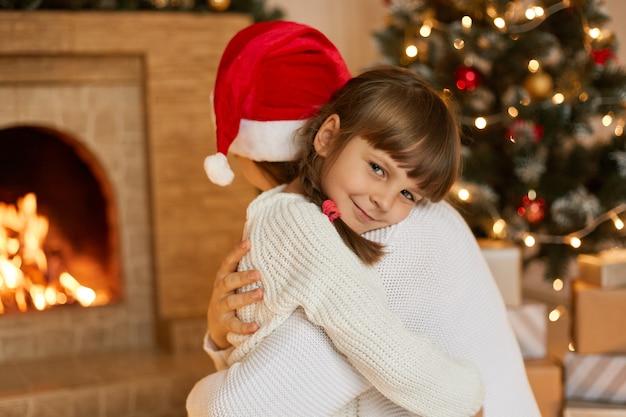 Heureuse jeune mère et petit enfant posant la veille de noël